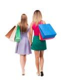 Задний взгляд 2 женщин с хозяйственными сумками Стоковое Изображение RF