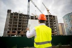 Задний взгляд инженера по строительству и монтажу смотря план здания Стоковые Фото