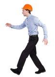 Задний взгляд идущего инженера в шлеме гуляя ванта в движении Стоковые Фото