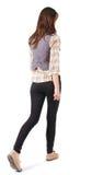 Задний взгляд идущей женщины в джинсыах Стоковые Фотографии RF