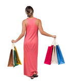 Задний взгляд идя женщины в женщине платья с хозяйственными сумками Стоковая Фотография RF