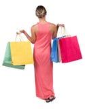 Задний взгляд идя женщины в женщине платья с хозяйственными сумками Стоковое фото RF