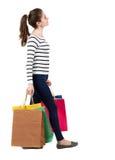 Задний взгляд идя женщины с хозяйственными сумками красивейшая девушка i Стоковое Изображение RF