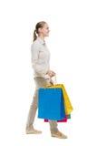 Задний взгляд идя женщины с хозяйственными сумками Стоковые Фото