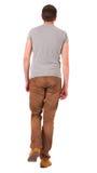 Задний взгляд идя красивого человека в джинсах и рубашке. Стоковые Фото