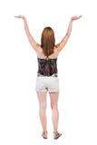 Задний взгляд красивой женщины в джинсах смотря стену и владения Стоковое фото RF