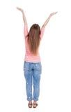 Задний взгляд красивой женщины в джинсах смотря стену и владения Стоковая Фотография