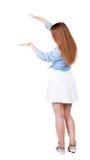 Задний взгляд красивой женщины в платье смотря стену и владения Стоковое Фото