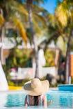 Задний взгляд красивой молодой женщины ослабляя в бассейне Стоковые Фотографии RF