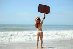 Задний взгляд красивой сексуальной молодой женщины держа surfboard в ее руке на пляже на предпосылке захода солнца или восхода со Стоковое фото RF