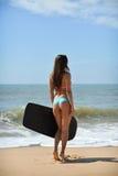 Задний взгляд красивой сексуальной молодой женщины держа surfboard в ее руке на пляже на предпосылке захода солнца или восхода со Стоковое Изображение