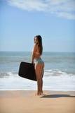 Задний взгляд красивой сексуальной молодой женщины держа surfboard в ее руке на пляже на предпосылке захода солнца или восхода со Стоковое Изображение RF