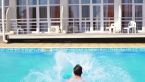 Задний взгляд молодого атлетического человека в заплыве замыкает накоротко ход и скакать к бассейну Slowmotion съемка видеоматериал