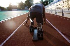 Задний взгляд молодого мужского спортсмена на начиная блоке стоковые фотографии rf