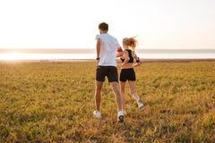 Задний взгляд молодого человека и женщины фитнеса делая jogging Стоковое фото RF