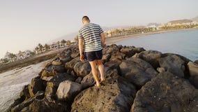 Задний взгляд молодого человека идя через утесы на пляже Укомплектуйте личным составом тратить время вне около моря в солнечном д сток-видео