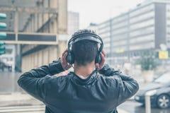 Задний взгляд молодого человека при наушники представляя в stre города Стоковые Изображения RF