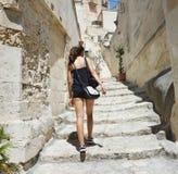 Задний взгляд молодой женщины взбираясь внутри к старому городку Matera Привлекательные di Matera Sassi посещения девушки путешес Стоковые Фото