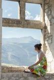 Задний взгляд молодой женщины в sundress смотря взгляд от окна Стоковая Фотография RF
