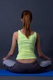 Задний взгляд молодой женщины сидя в положении лотоса над серым цветом Стоковое Изображение RF