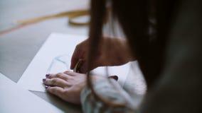Задний взгляд молодой женщины стирая на бумаге с эскизом голубых ботинок Дизайнер сидя на таблице и превращаясь плане 4K акции видеоматериалы