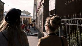 Задний взгляд молодой творческой женщины 2 идя в центр города и говорить Творческие архитекторы обсуждая проект сток-видео