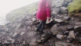 Задний взгляд молодой туристской женщины взбираясь на горе в дождливом дне Женщина исследуя новое место движение медленное сток-видео