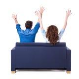 Задний взгляд молодых жизнерадостных пар сидя на софе изолированной на w Стоковое Изображение RF