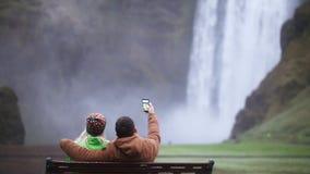 Задний взгляд молодых пар сидя на стенде и принимая фото selfie на smartphone водопад skogafoss Исландии сток-видео