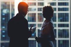 Задний взгляд молодых успешных финансистов человека и женщины стоя с цифровыми таблеткой и мобильным телефоном в интерьере офиса Стоковые Фото
