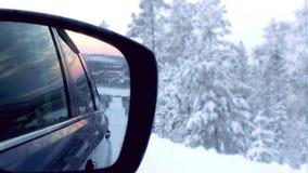 Задний взгляд на зеркале автомобиля на дороге зимы Стоковая Фотография