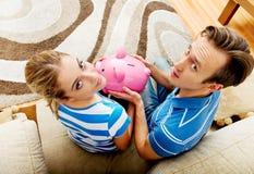 Задний взгляд пар сидя на софе с копилкой Стоковое Фото