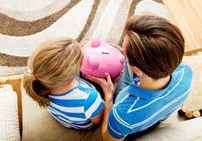 Задний взгляд пар сидя на софе с копилкой Стоковые Фотографии RF