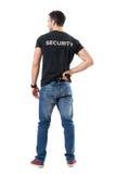Задний взгляд предупрежденных полисмена или агента безопасности прикрытия достигая оружие руки прикрепленное на поясе Стоковые Изображения