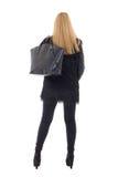 Задний взгляд привлекательной ультрамодной женщины в теплых одеждах с handba Стоковая Фотография