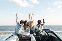 Задний взгляд друзей стоя с поднятыми руками приближает к автомобилю стоковое изображение rf