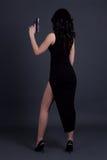 Задний взгляд сексуального тайного агента женщины представляя с оружием над серым цветом Стоковые Фотографии RF
