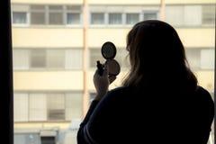 Задний взгляд силуэта женщины кладя на состав перед Стоковые Фото