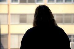 Задний взгляд силуэта женщины кладя на состав перед Стоковое Фото