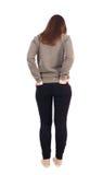 Задний взгляд стоять молодая красивая женщина в джинсах Стоковое фото RF
