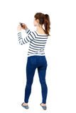 Задний взгляд стоять молодая красивая женщина используя передвижное pho Стоковое Изображение RF