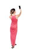 Задний взгляд стоять молодая красивая женщина используя передвижное pho Стоковые Фото