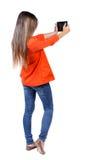 Задний взгляд стоять молодая красивая женщина используя передвижное pho Стоковая Фотография RF