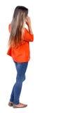 Задний взгляд стоять молодая красивая женщина используя передвижной phon Стоковая Фотография RF
