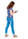 Задний взгляд стоять молодая красивая женщина используя передвижной phon Стоковое Изображение RF