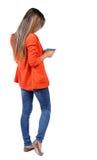 Задний взгляд стоять молодая красивая женщина используя передвижной phon Стоковые Изображения