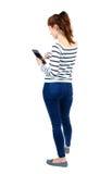 Задний взгляд стоять молодая красивая женщина используя передвижной phon Стоковые Фотографии RF