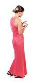 Задний взгляд стоять молодая красивая женщина используя передвижной phon Стоковое Изображение