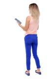Задний взгляд стоять молодая красивая женщина используя передвижной phon Стоковое Фото