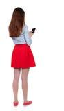 Задний взгляд стоять молодая красивая женщина используя передвижной phon Стоковые Фото